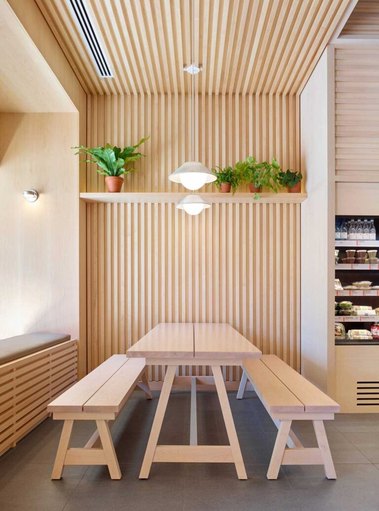 Tambour strips of wood line the walls and slide up to the ceiling, extending the long appearance of the picnic table in the sandwich cafe.