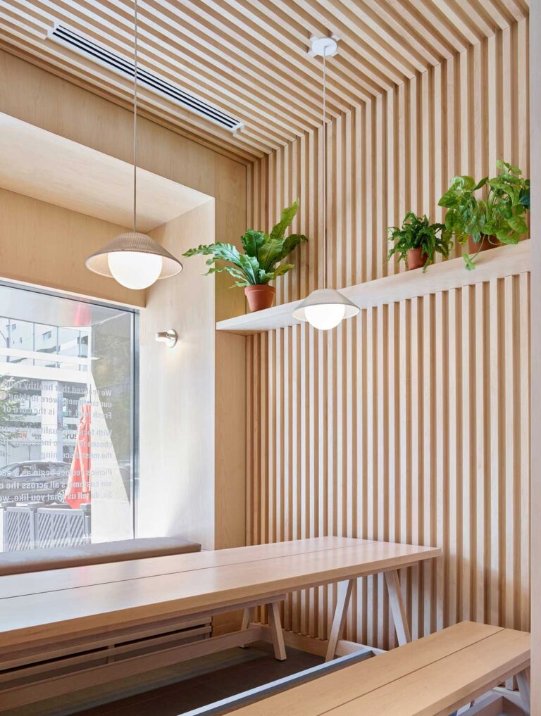 Detail view of tambour walls and ceiling with two modern pendant lamps overhead. A shelf of plants adds to the biophilic warmth of the space.