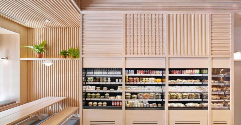 The wall of chilled prepared foods at this grab and go cafe has a detail of wood slats overhead.
