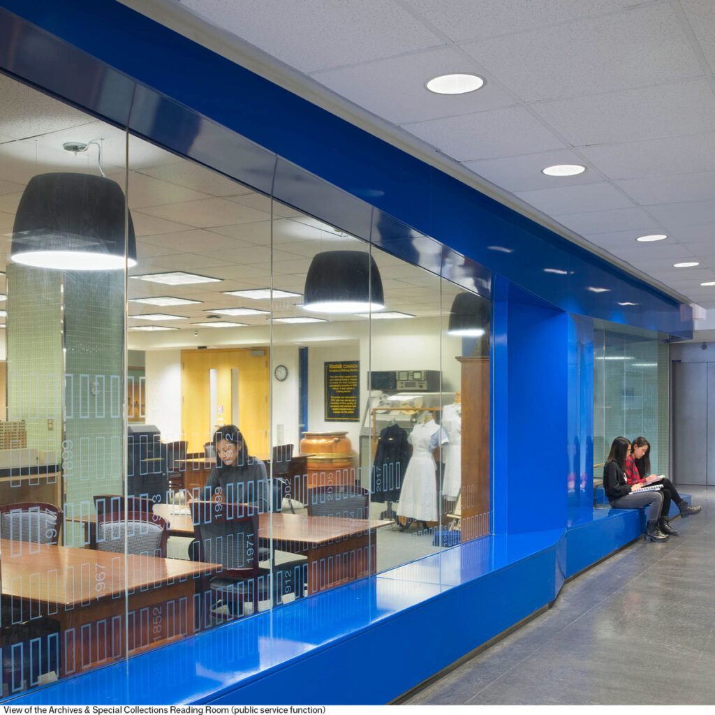 A blue metal panel with windows provides a storefront display with cutouts where passers by can sit.