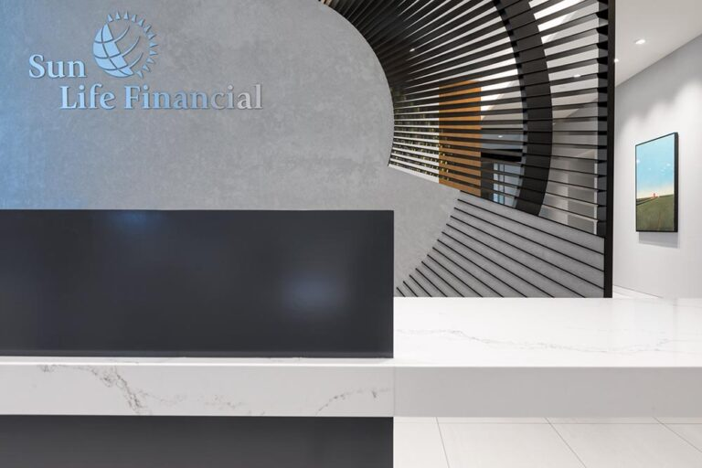 Reception desk with black desk and long pale marble countertop in front of a screen with a radiating detail.
