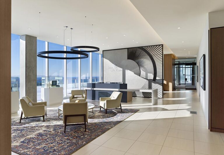 Reception area next to a wall of windows, with seating area of four armchairs. A screen with a radiating arc is behind the reception desk.