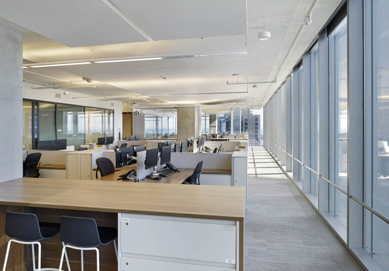 Windows wrap around an open concept office with collaboration space.