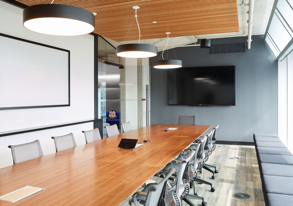A large meeting room with wood topped conference table surrounded by office chairs and bench seating nearby. Round black pendant lights overhead extend the brand while a tambour wood screen hides acoustical panelling.