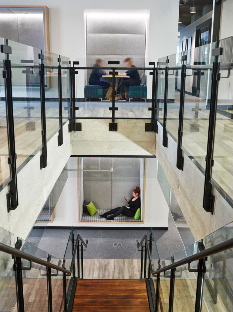 View down a set of connecting stairs with glass partitions and black metal supports.