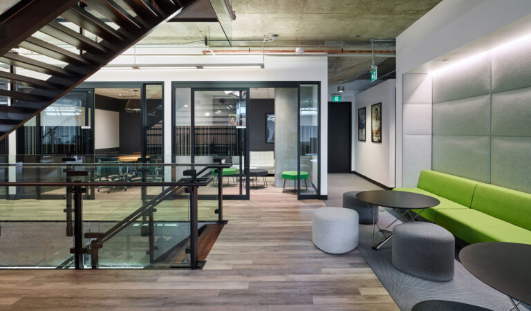 Open lounges surround the stair, with green and gray seating and adjacent glasswalled meeting rooms.