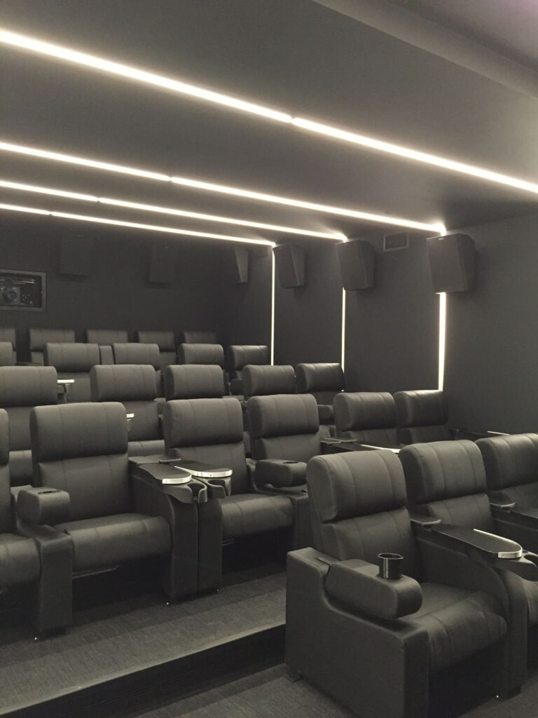 Employee screening area with black walls, surround sound and rows of comfy cinema seats.