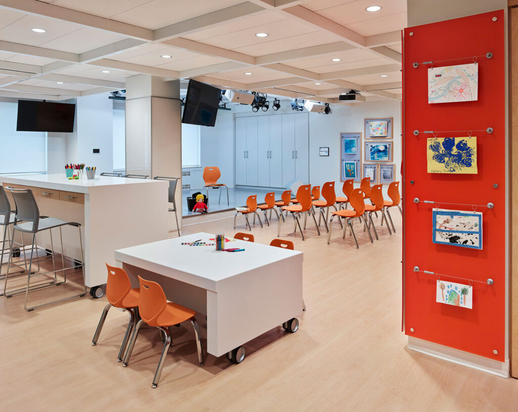 Creative arts studio with low and high moveable furniture, rows of moveable seating and space to display art.