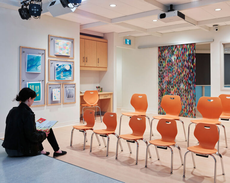 A woman sits on the corner of the stage with a row of chairs facing and a colourful sliding door opposite hides another part of the space.