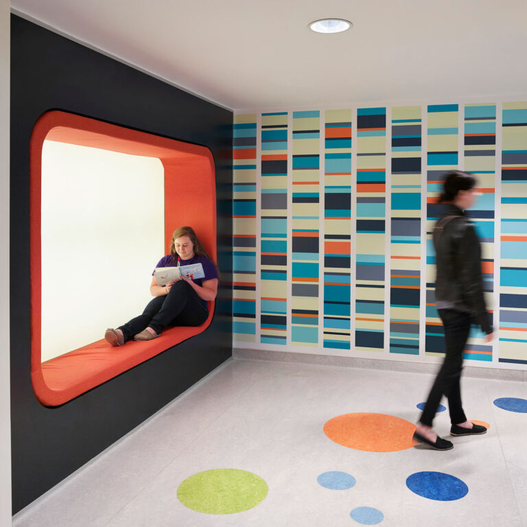 A padded orange alcove provides a seating nook next to a blue, orange and yellow linear graphic on the wall.