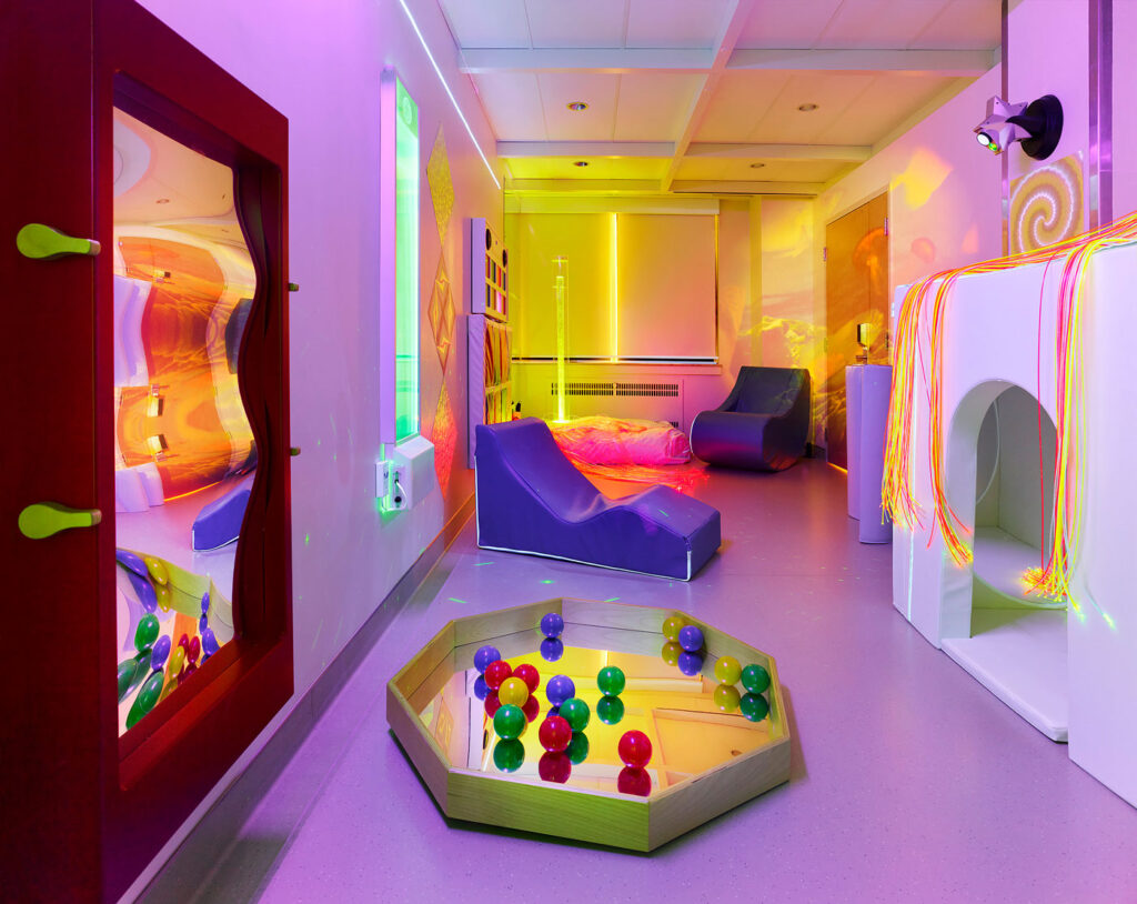 Sensory stimulation room with soft chairs, surfaces that light up and balls in a mirrored pond.