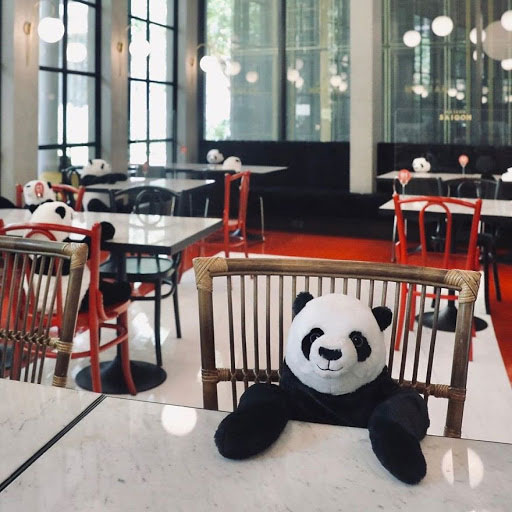 A stuffed panda sits at a restaurant table in the foreground, with an empty restaurant behind him.