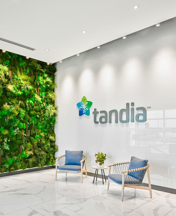 Reception area at Tandia Financial with a living wall, and a raised logo sign above two chairs.