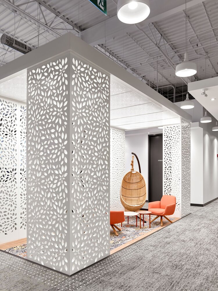 A casual meeting area is demarcated by a white perforated screen, giving textured interest to this office space.