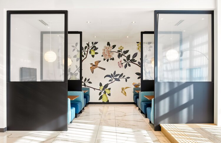 Meeting space with a floral wallpaper along the far wall and booth seating areas.