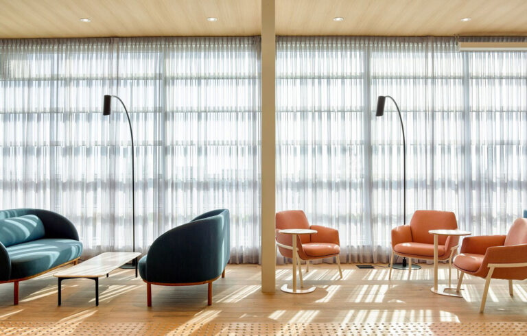 Teal and coral chairs are placed in two seating arrangements against a curtained window.