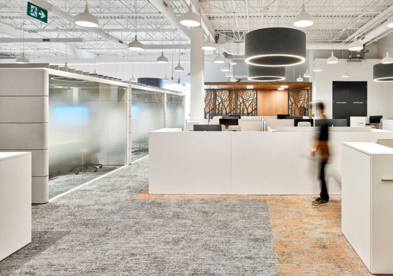 A woman passes through an office area with textured pale gray carpeting and wood floors. White desk areas demarcate staff space.