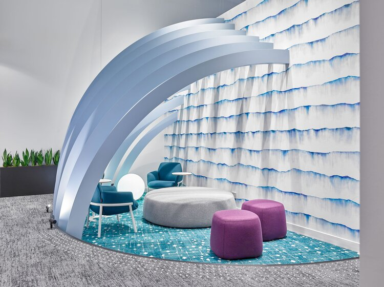 A curved feature element creates a cozy space for staff to quickly meet with fuzzy blue carpeting.