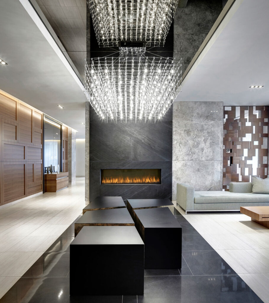 Sleek black coffee tables are arranged together organically under a filament filled geometric chandelier.