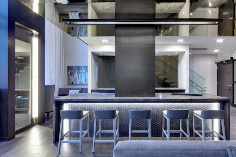 Kitchen amenity space with waterfall marble counter, pale gray bar stools and reflective ceiling.