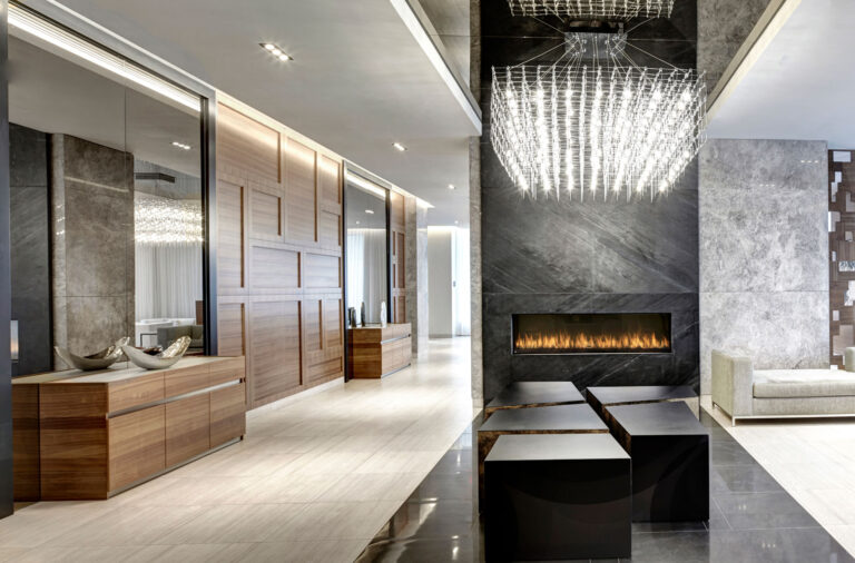 A condo lobboy with pale stone floors, warm wood panelling and a fireplace surrounded by black stone.