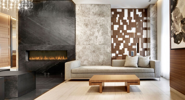 A condo lobby with long pale couch, next to a fireplace surrounded by black stone.