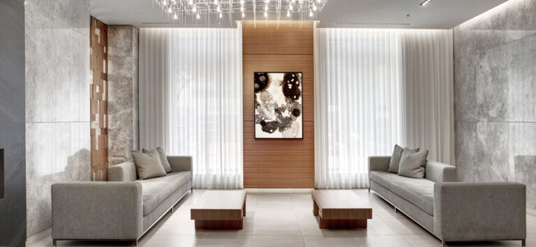 Lounge in condo lobby with two gray couches opposite each other, with gray stone walls and white curtains to provide privacy.
