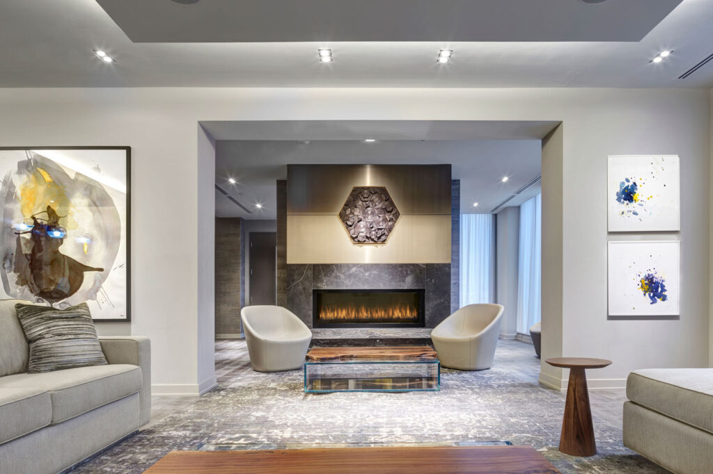 Condo lobby seating area with two chairs opposite fire place and a hexagonal piece of art made of wood.