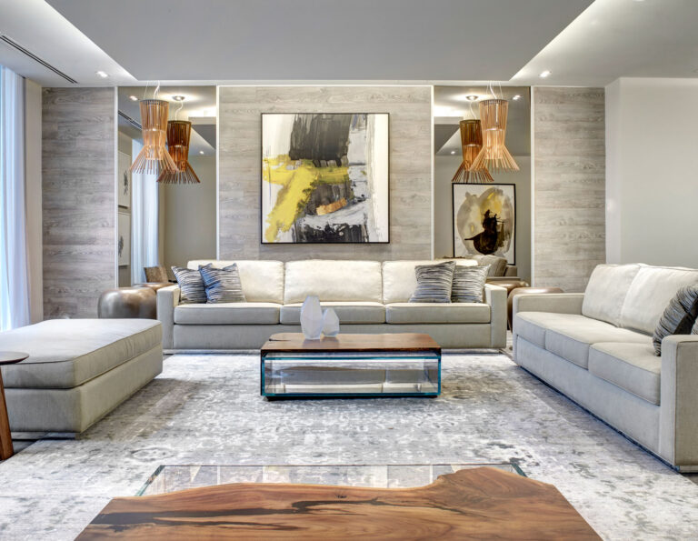 Large seating area in this condo lobby with pale gray couches, gray wood panelled walls and abstract black and yellow art.