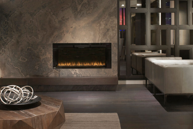 A cozy fireplace is set into a beautiful marble slab against a wall of mirrors.
