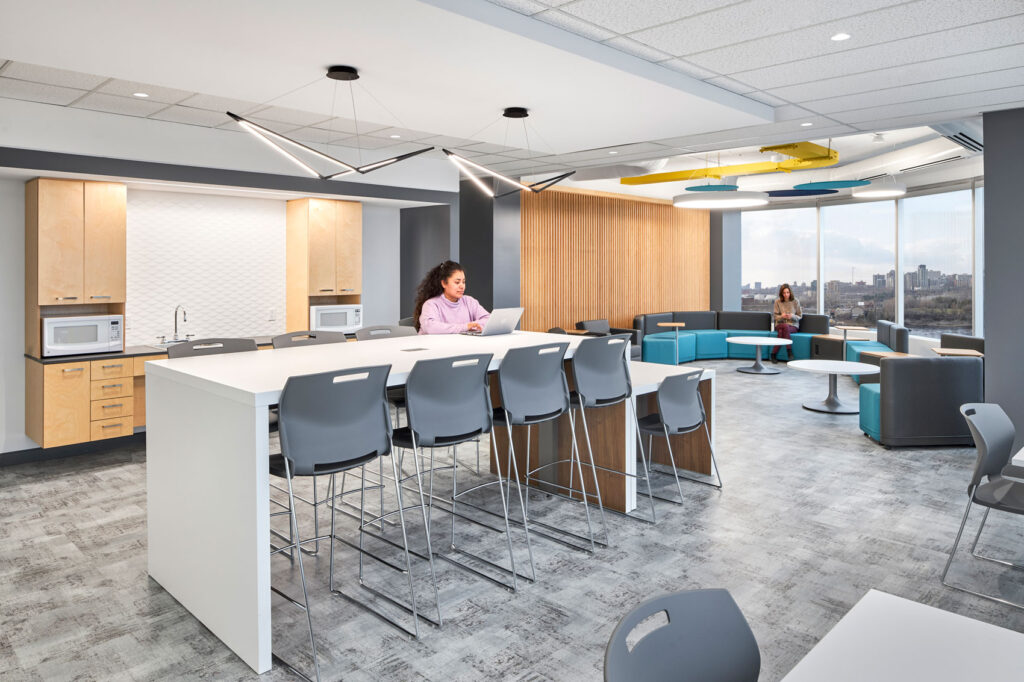 The employee cafeteria has spaces to re-heat lunch, and several high top seating areas and an adjacent casual seating area.
