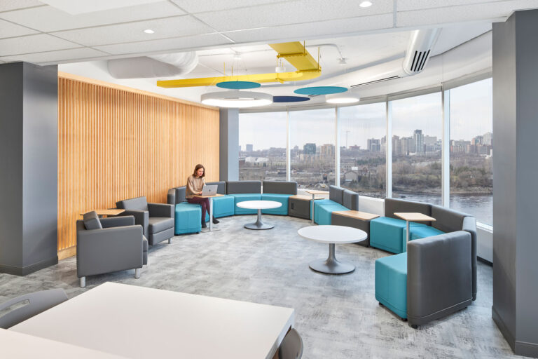 A casual meeting space has flexible seating, natural tambour walls and acoustical panelling to absorb sound.