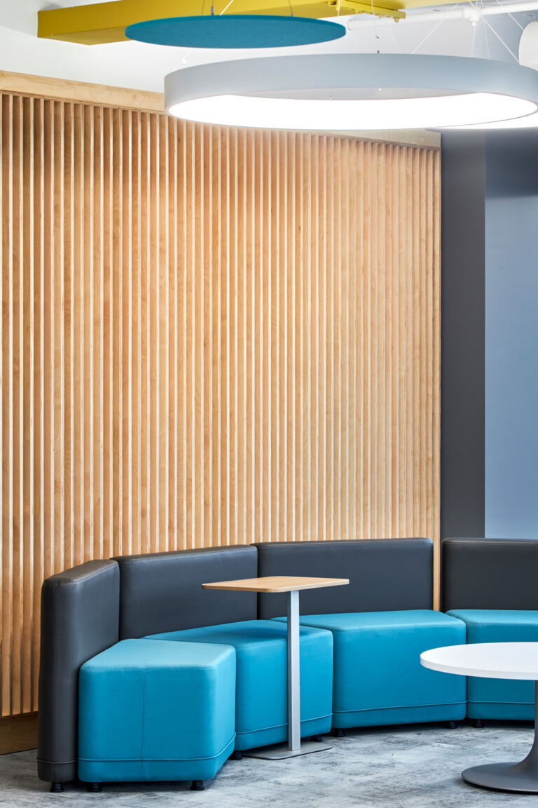 A curved seating area is lined with tambour walls and bright acoustical elements above.