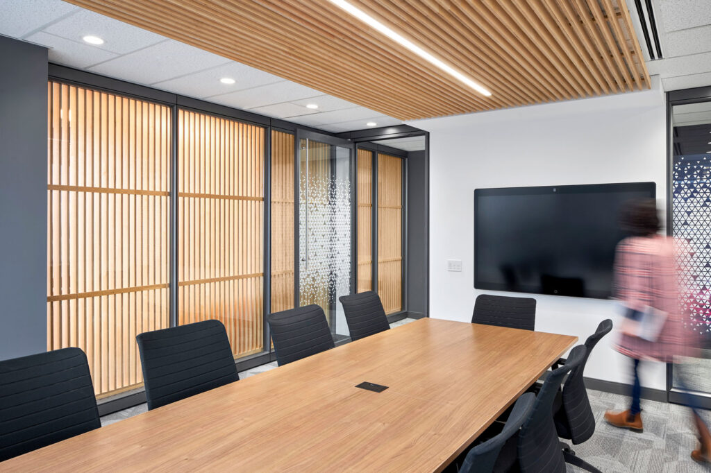 A boardroom ceiling is lined with tambour walls which echo the maple wood of the table.