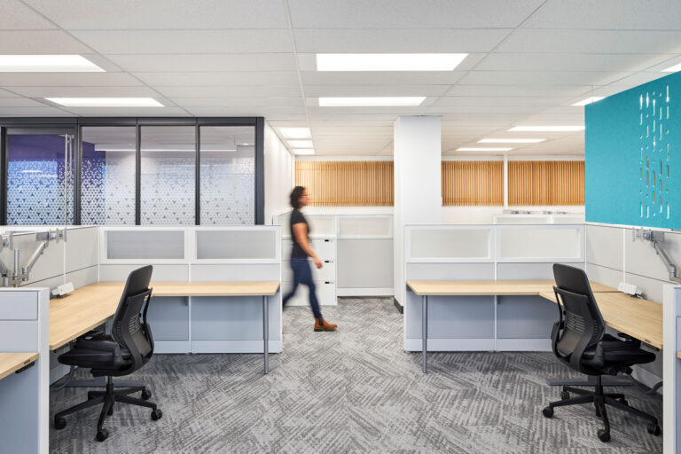 A woman walks by two desk spaces with tambour walls, and a turquoise acoustical panel.