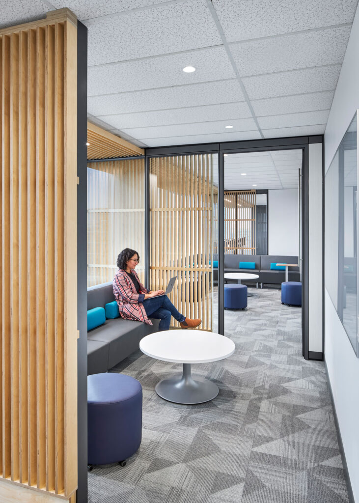 An employee works from an anteroom lined with tambour wood walls.
