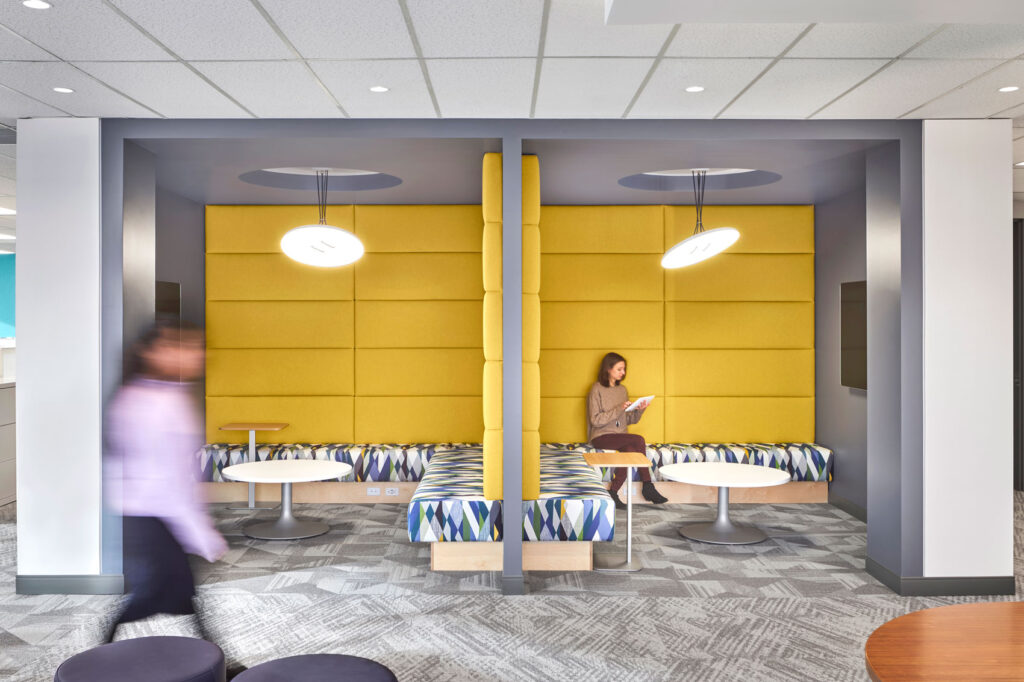 Two both seating areas with a plush wall in between are covered in bright yellow upholstery with geometric patterned seating.