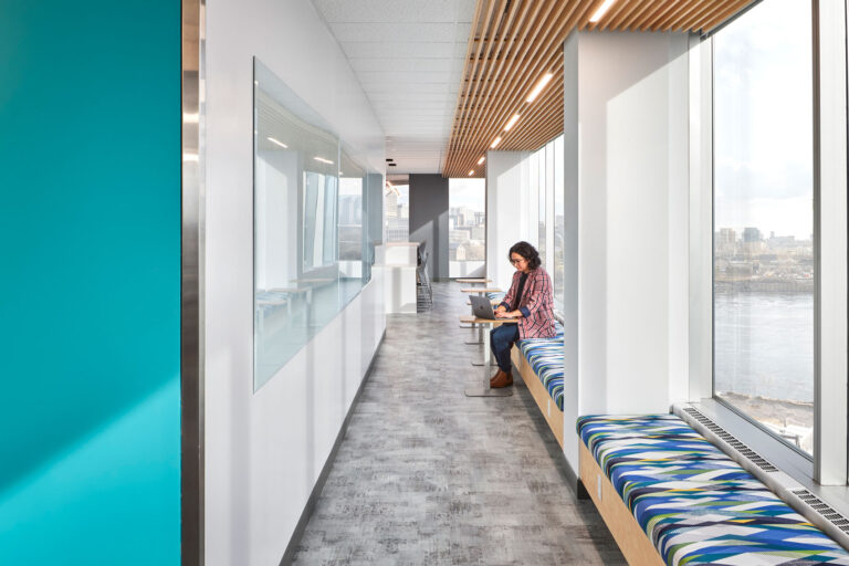 Upholstered benches line a hallway of windows, providing a space for employees to work in a bright, naturally lit space.