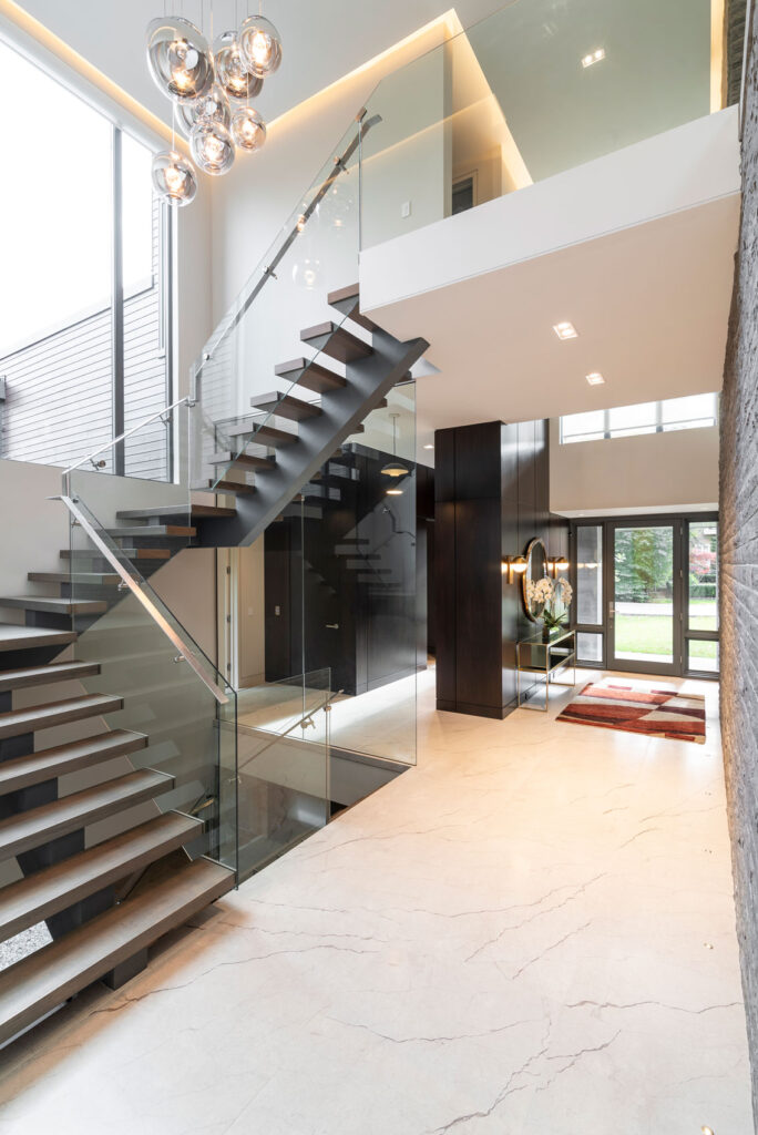 A sleek and modern entry way welcomes guests to the home and up a slate gray staircase with open risers.
