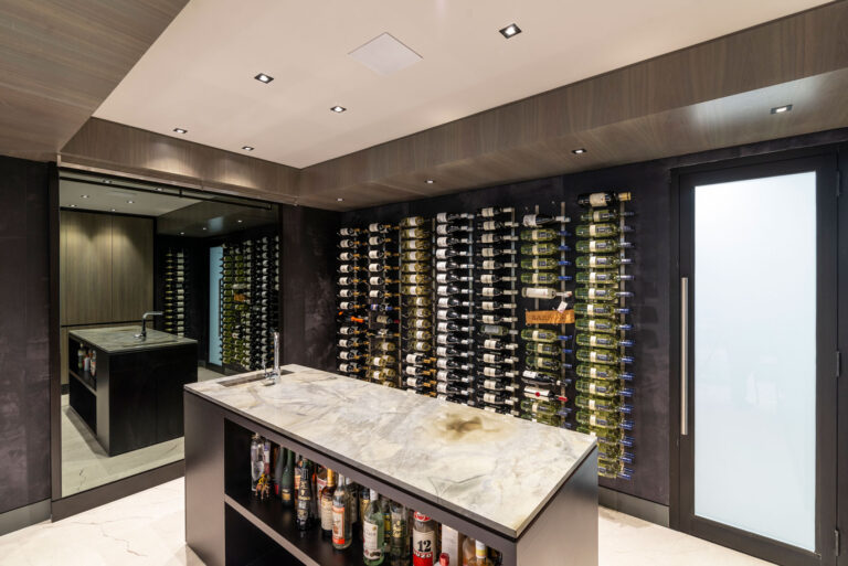 Inside a wine tasting room with bottles racked horizontally against a long black wall.