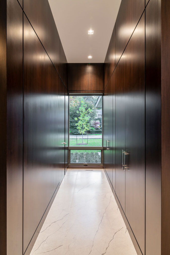 A long wood panelled hallway provides ample storage with an outdoor window at the end of the hall.
