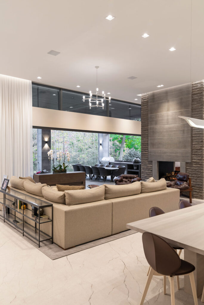 A vast family room with a slate sided fireplace is a focal point for an enormous beige leather sectional couch.