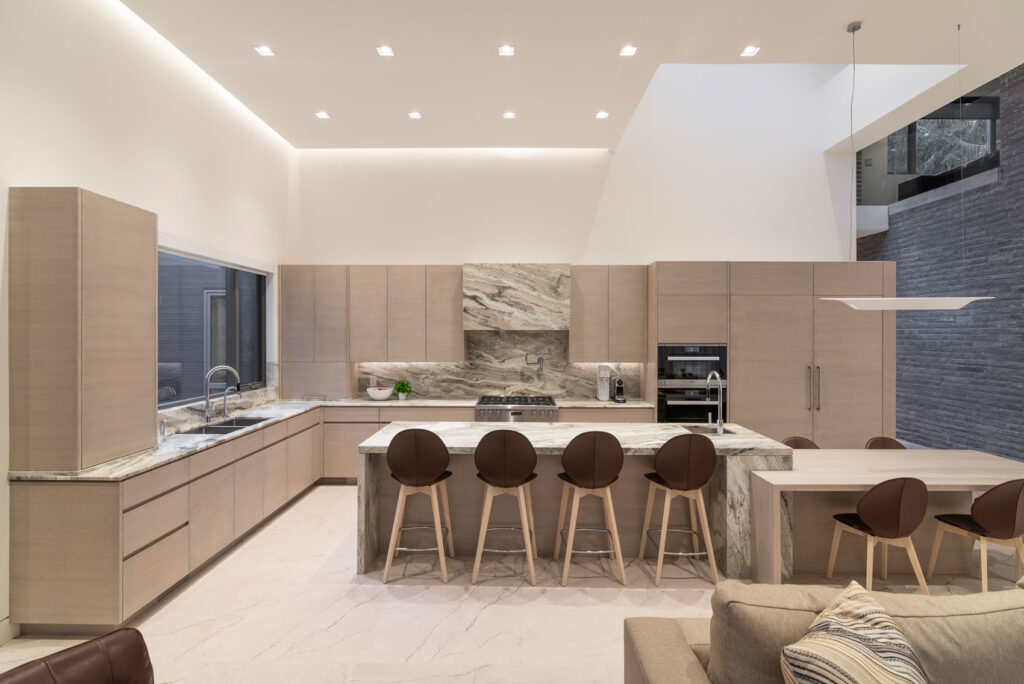A vast kitchen with pale panelling is the backdrop for a long island with two heights and bar sink.