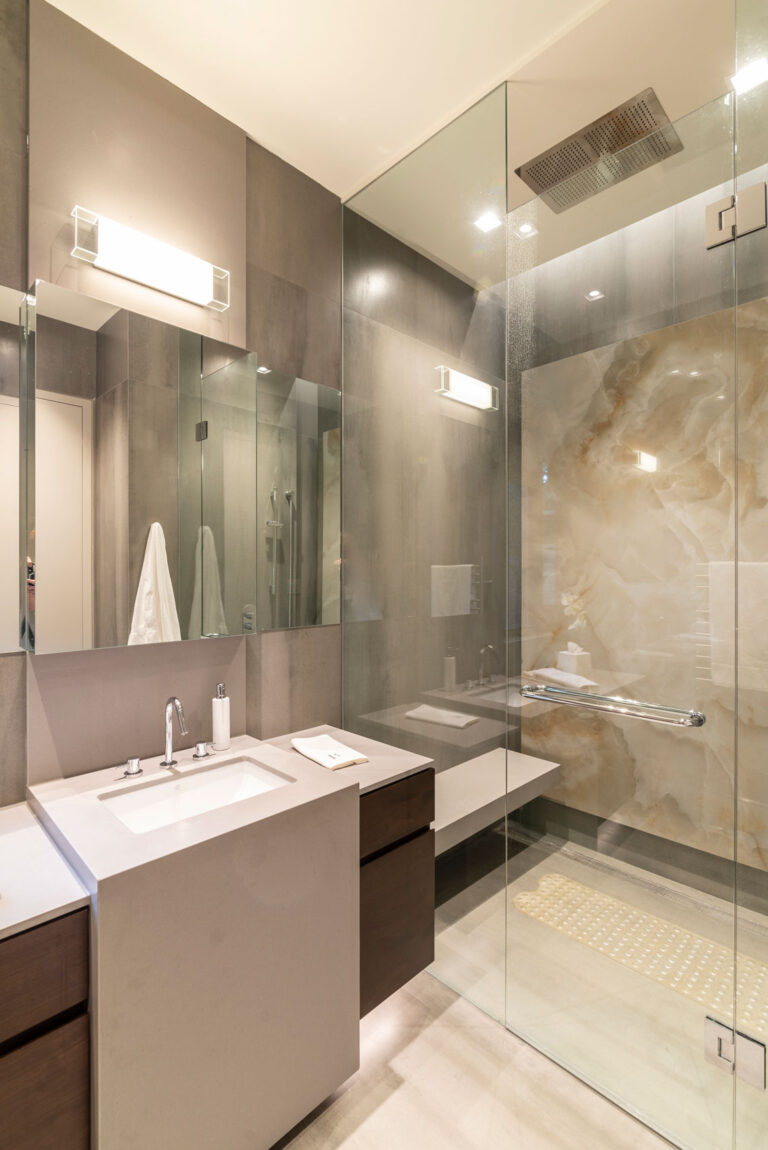 A modern bathroom with glass shower door, sink framed in marble with wood drawers inside.