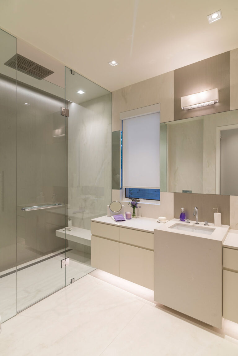Serene and angular bathroom with shower and white panelled sink.