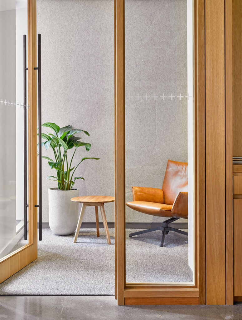 A tranquil view of a small meeting or phone room with a leather chair, low stool table and lush green plant.