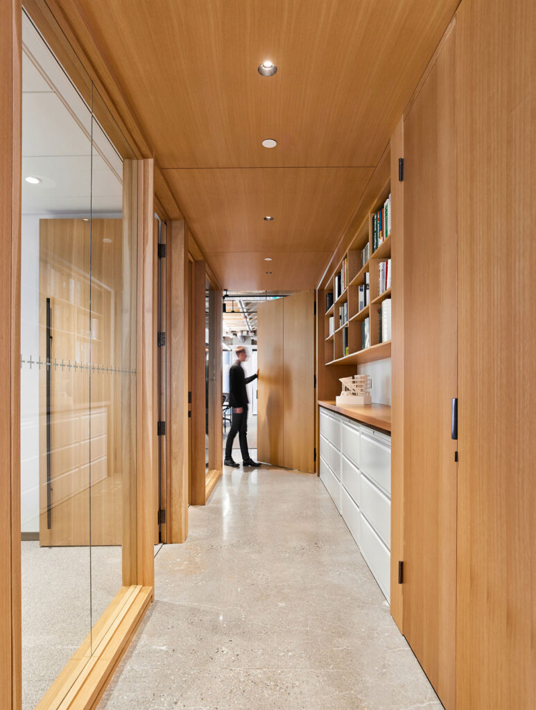 A corridor lined in maple wood with several glass walled meeting rooms opposite shelving and file space.