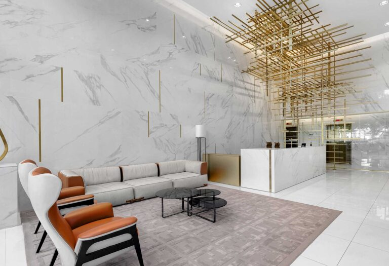 A gold scuplture of cross hatched bars hangs over the white marble reception desk in a condo lobby.