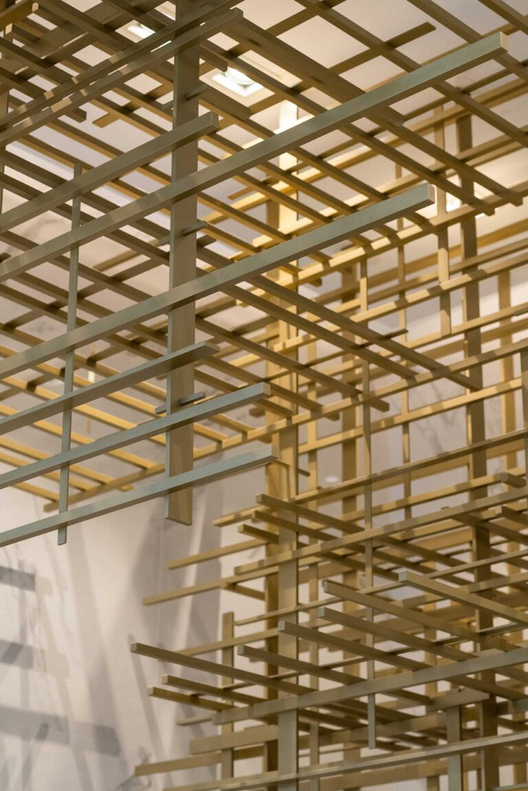 Detail view looking up at the gold scuplture of cross hatched bars, making an artistic grid.