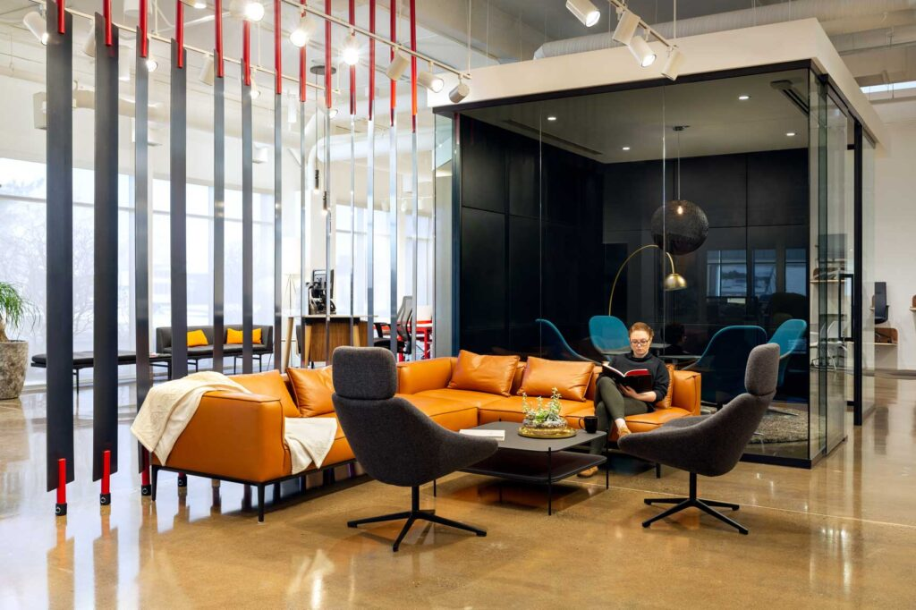 An orange couch with black armchairs becomes a cool place to meet against a wooden slat installation.